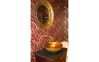 A deep wall color in a dark powder room adds depth and drama. Powder Room designed by Barbara Sternau Interior Design.