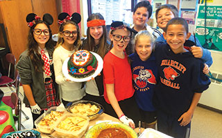 Briarcliff Middle School Spanish students pose with the Mexican food they made for El Dia de los Muertos.