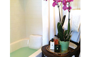 Create a mini-spa in your bathroom with a scented candle, luxurious bath oils, and a plush terrycloth bath pillow.