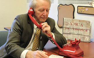 Civic leader, Paul Schwarz, the son of Volunteer New York! Co-founder, Jane Schwarz, seen here recreating the first ever volunteer-to-nonprofit connection made 65 years ago at a borrowed desk at the YMCA of White Plains. Photo Credit: Volunteer New York!