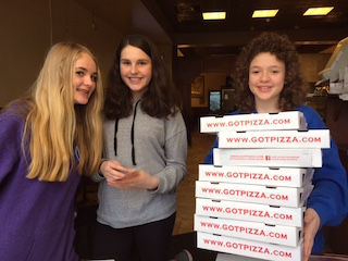 Middle school students place stickers on boxes at Nick's Pizza & Capri Pizza.