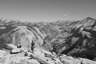 Two hikers pause to take in the seemingly unending  Yosemite Valley, California after a taxing journey to the summit of Half Dome.