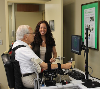 A stroke survivor utilizing wrist robot for functional wrist and hand motion with Avrielle Rykman Peltz, Chief Operating Officer of the Restorative Neurology Clinic.