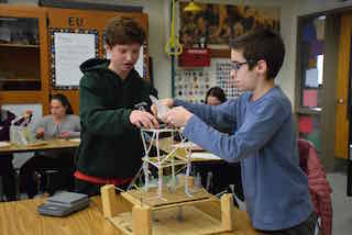 Irvington Middle School eighth-graders Henry Demarest and Nicholas Papapanou prepare their structure before its stability is tested in a simulated seismic event.