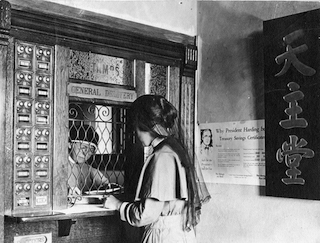 Sister Katherine Slattery at work in the Maryknoll Post Office (c. 1920s).