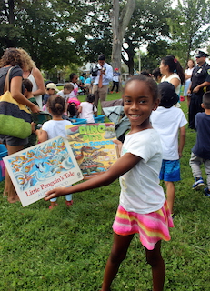 Six-year-old Eden Woodley shows off the books she chose at the Ossining Bookmobile event in Nelson Sitting Park.