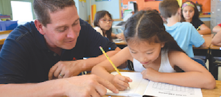Dows Lane Elementary School teacher Christopher Cullen assists third-grader Ella Liu with a writing assignment on the first day of school on September 5.