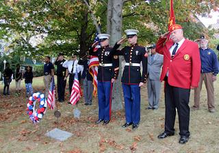 Veterans and members of the military salute during the ceremony for Craig Wyche at Ossining High School.