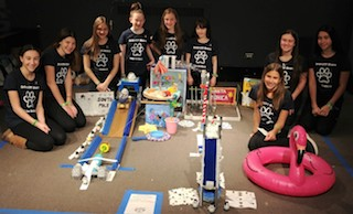 Eighth graders used their imaginations to create an intricate Rube Goldberg machine to pour cereal. Goldberg's granddaughter, Jennifer George, congratulated the students.